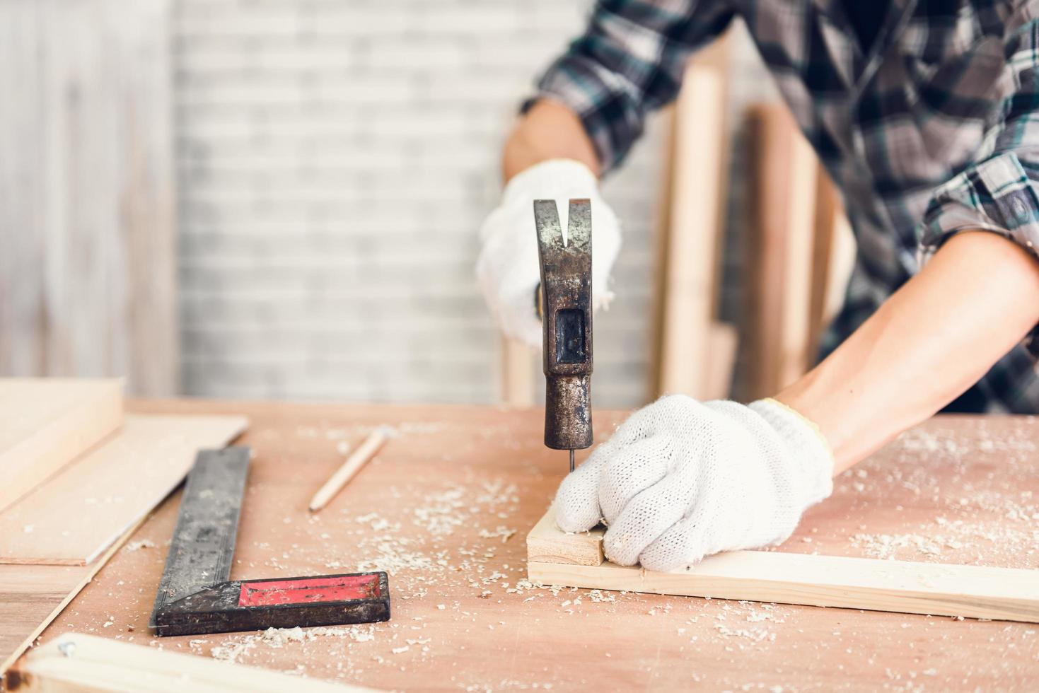 uomo che martella chiodo nel legno foto
