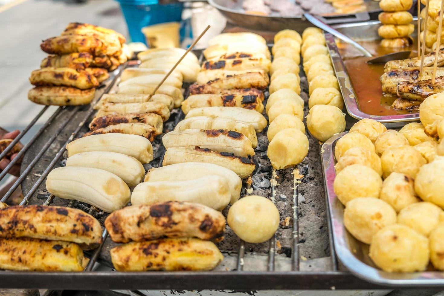 banana alla griglia e patate dolci per la vendita in un mercato locale foto