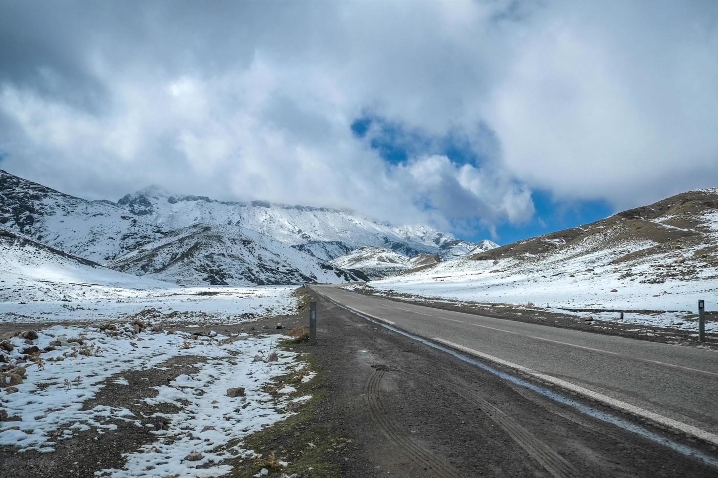 una strada in mezzo alla catena montuosa innevata foto