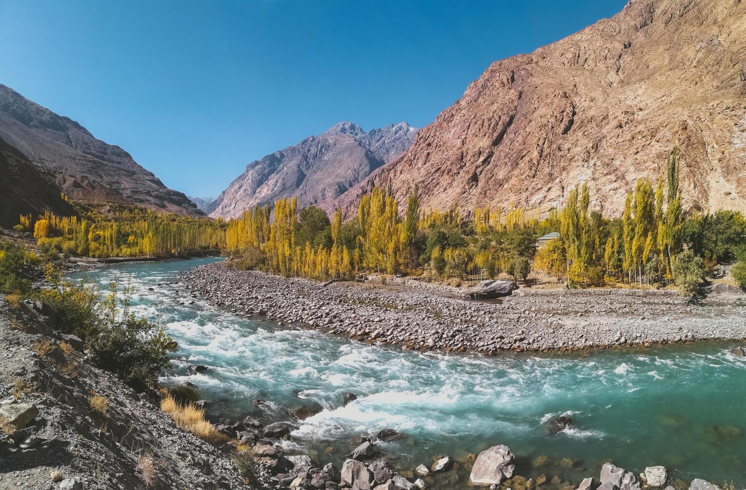 fiume tortuoso che scorre attraverso la catena montuosa indù Kush in autunno foto