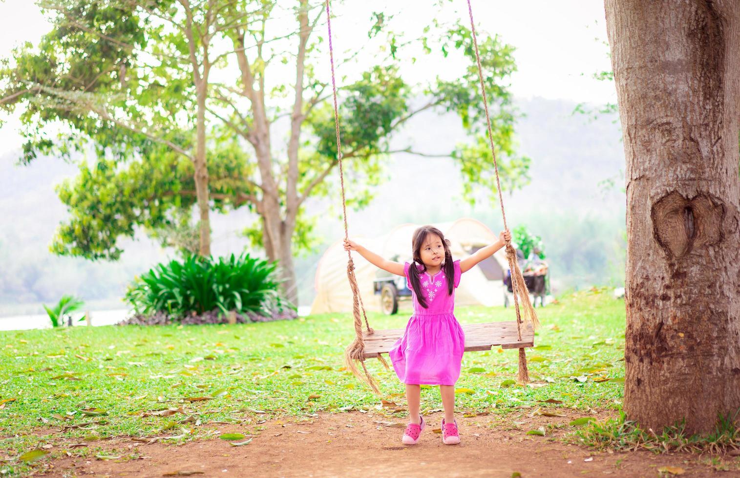 giovane ragazza asiatica nell'oscillazione dell'albero foto