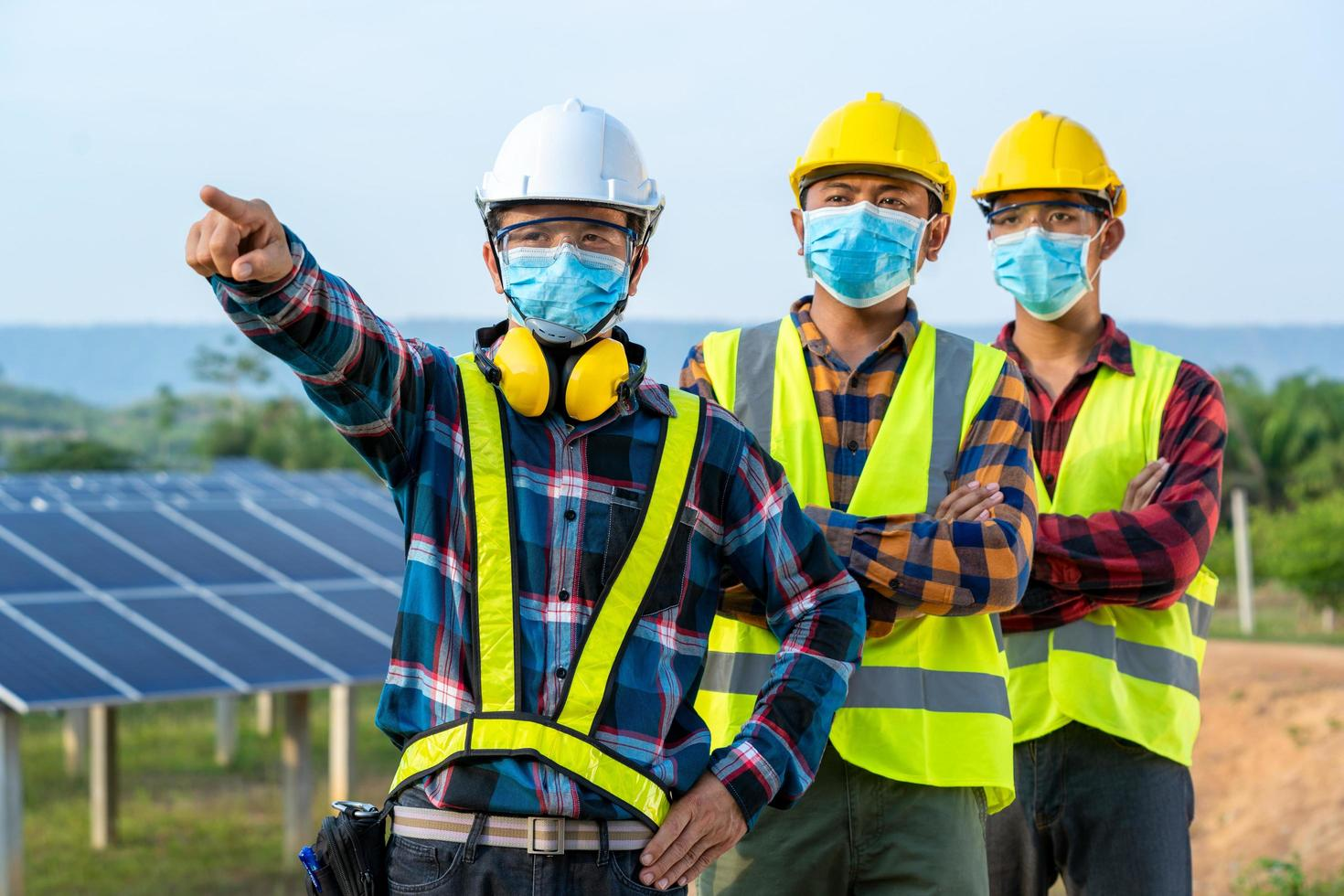 operai mascherati accanto al pannello solare foto