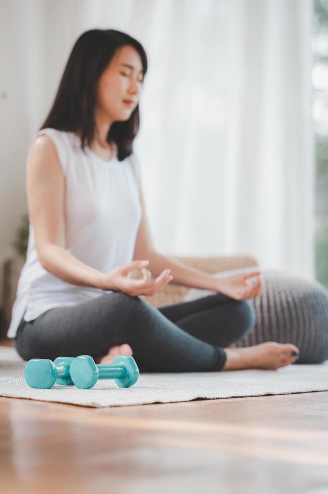 Dumbbelsl sul pavimento con la donna che fa meditazione foto
