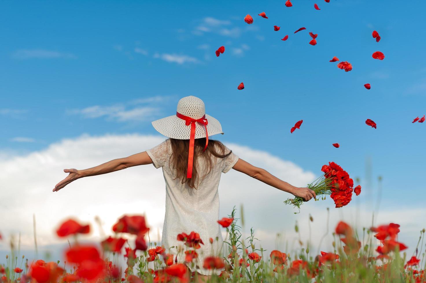 donna con cappello bianco e vestito si erge a braccia aperte foto
