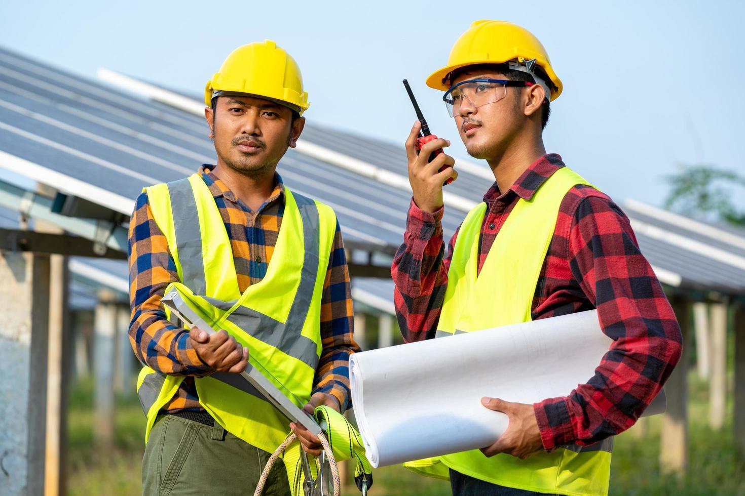 uomini che indossano attrezzature di sicurezza accanto ai pannelli solari foto