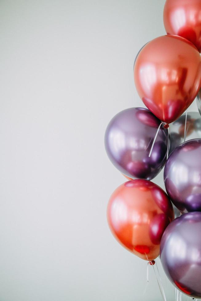 palloncini rossi e viola su superficie bianca foto