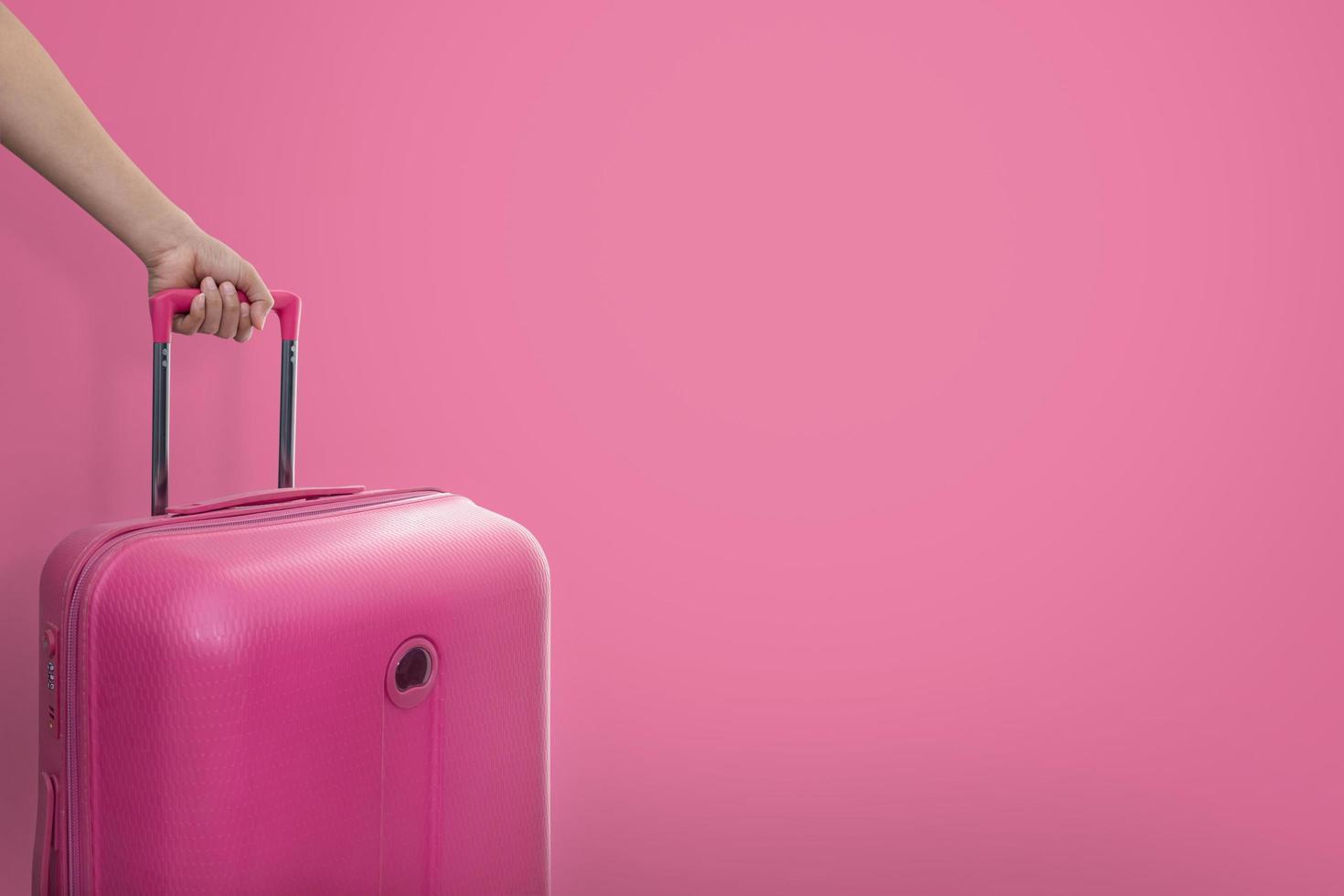 mano che tiene la valigia rosa foto