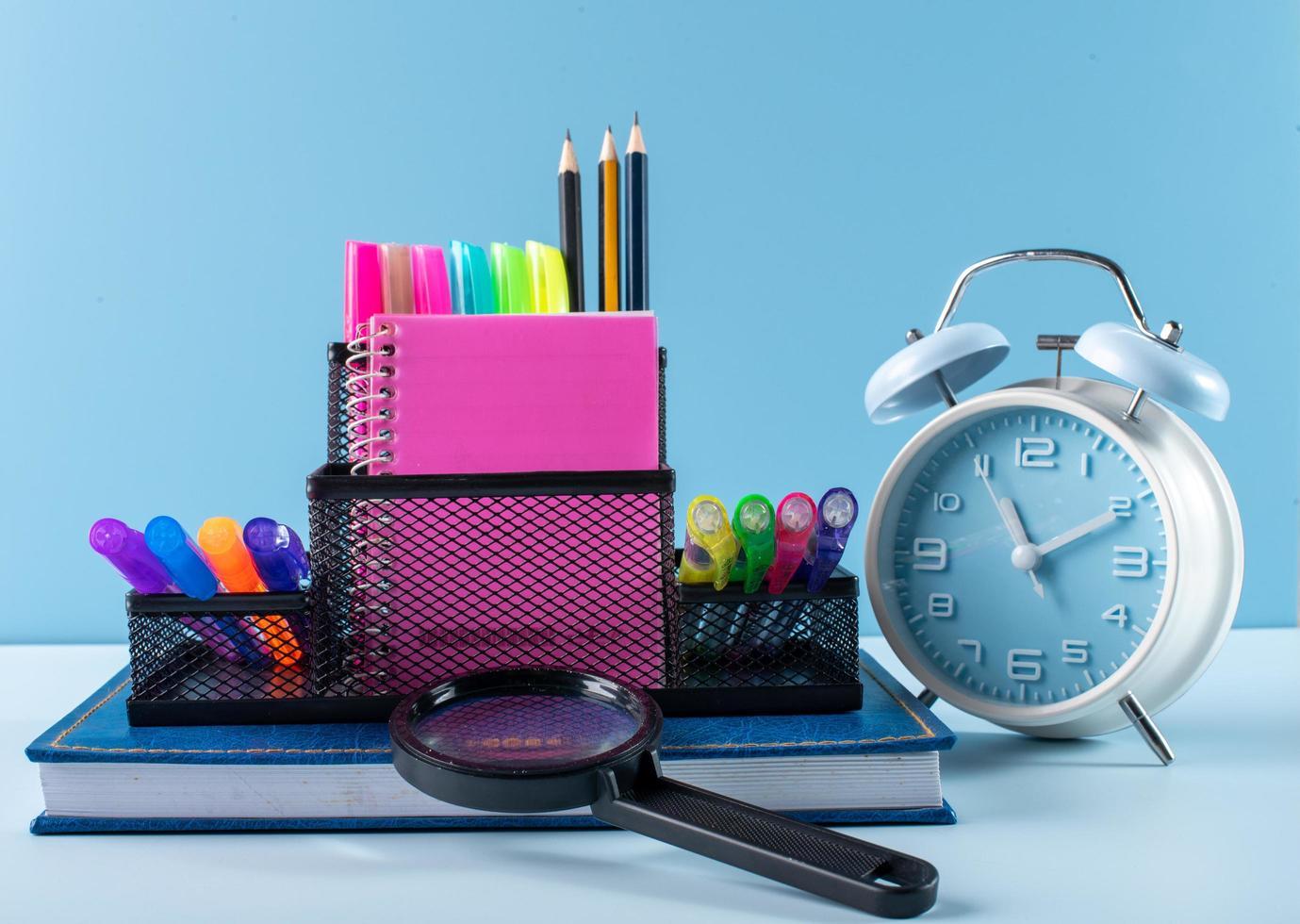 materiale scolastico e sveglia su sfondo blu foto