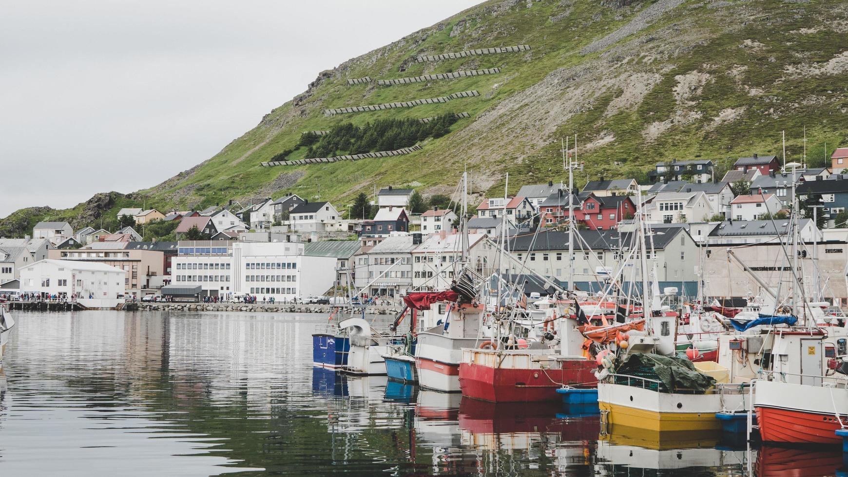 barche ormeggiate con edifici e montagne foto