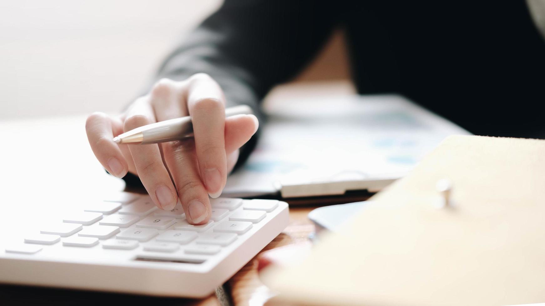 stretta di imprenditrice utilizzando la calcolatrice foto