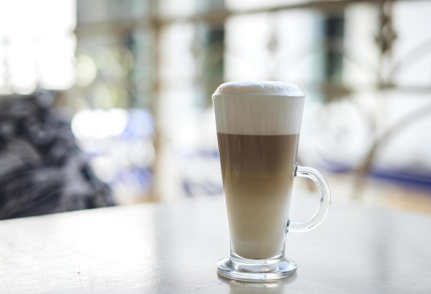 latte in tazza trasparente sul tavolo foto