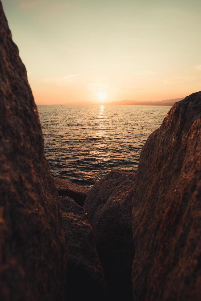 tramonto e acqua visti tra le rocce foto