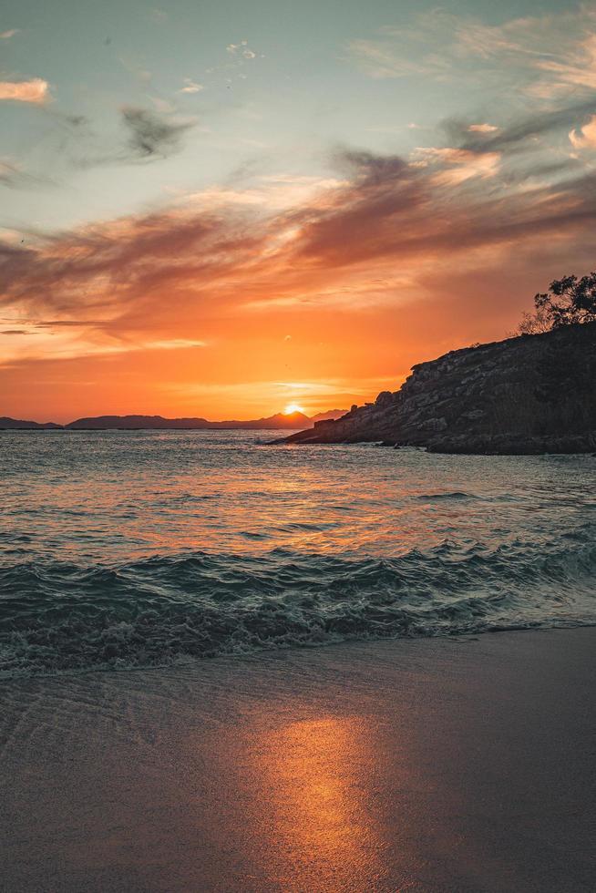 sabbia, acqua, montagna e cielo colorato all'alba foto