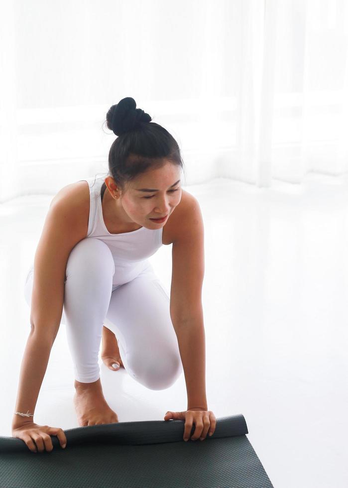 donna arrotolando materassino yoga foto