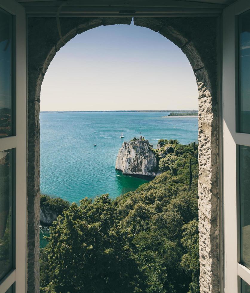 alberi, rocce e specchio d'acqua visti attraverso la finestra foto