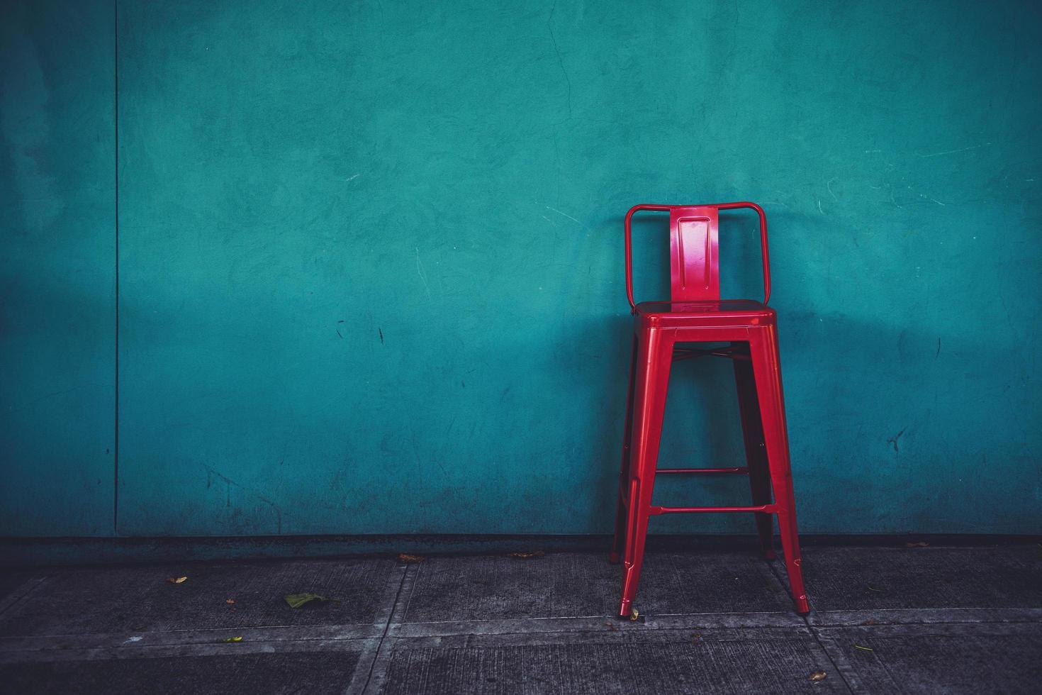 sedia in metallo rosso contro il muro blu foto