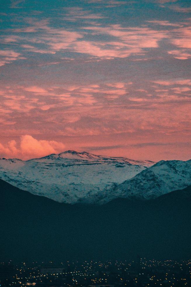 montagna coperta di neve sotto le nuvole del tramonto foto
