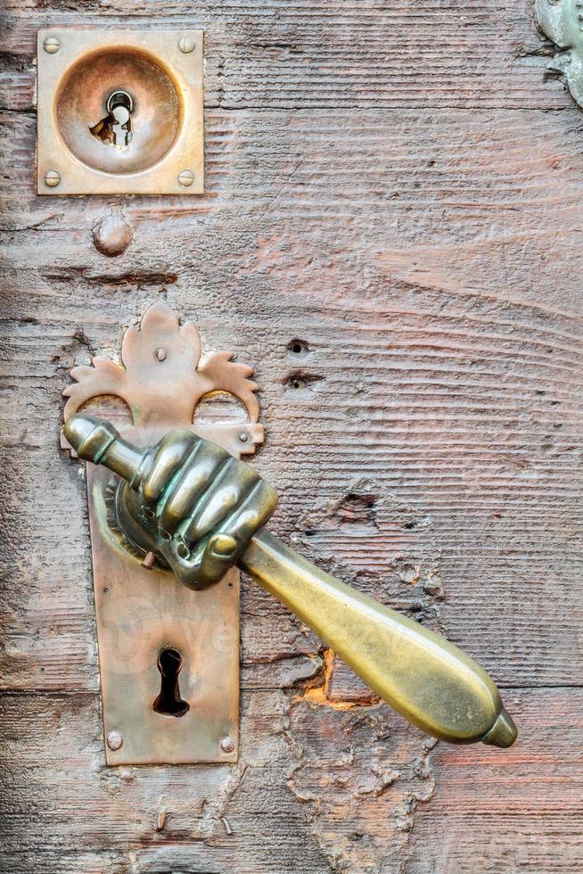 maniglia a forma di mano d'epoca sulla porta antica, sfondo foto