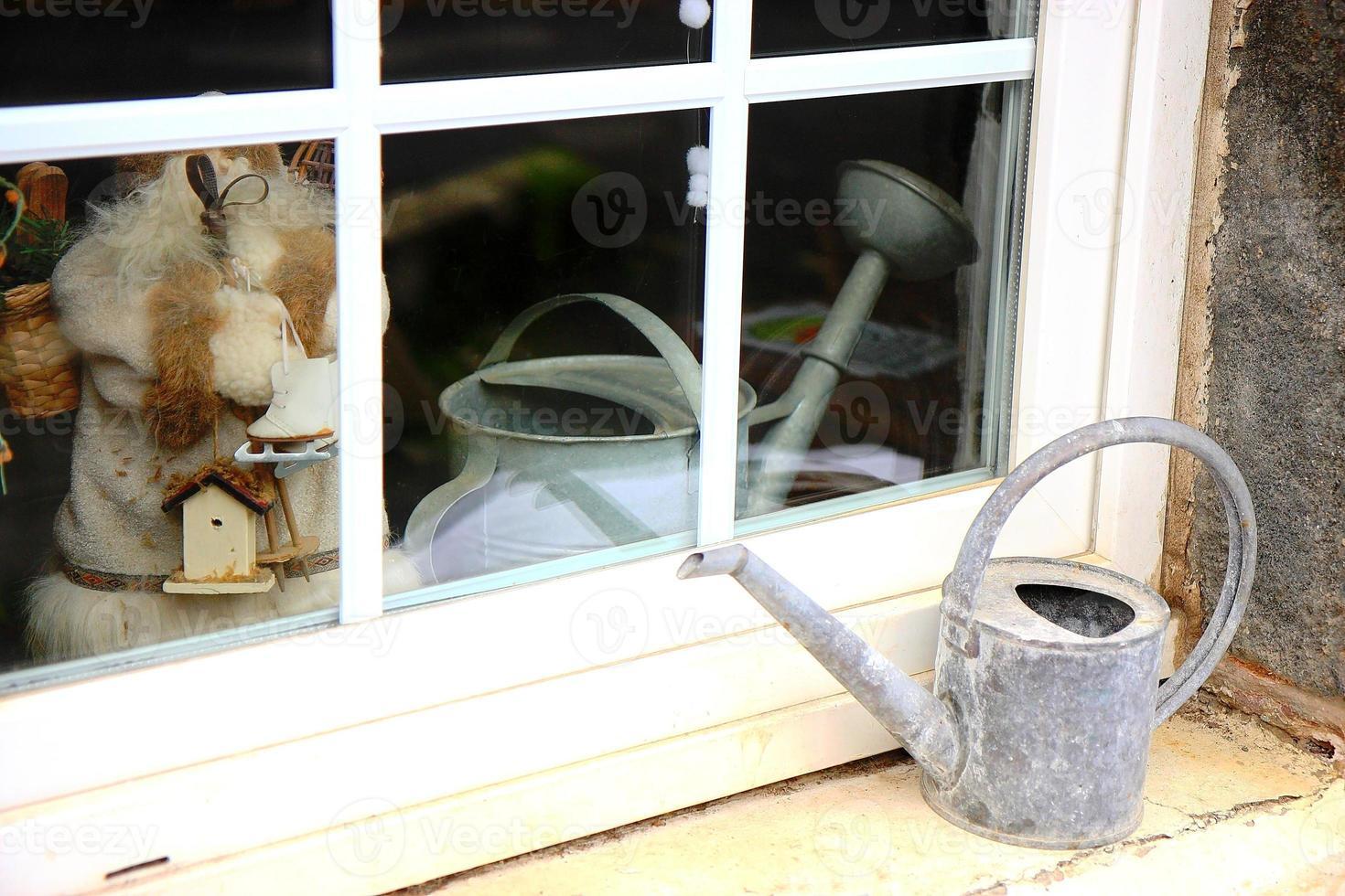 annaffiatoio sul davanzale della finestra foto