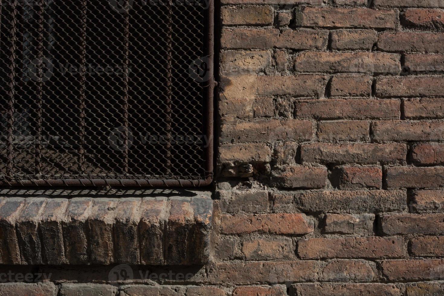 muro di mattoni e struttura del cancello di metallo arrugginito foto