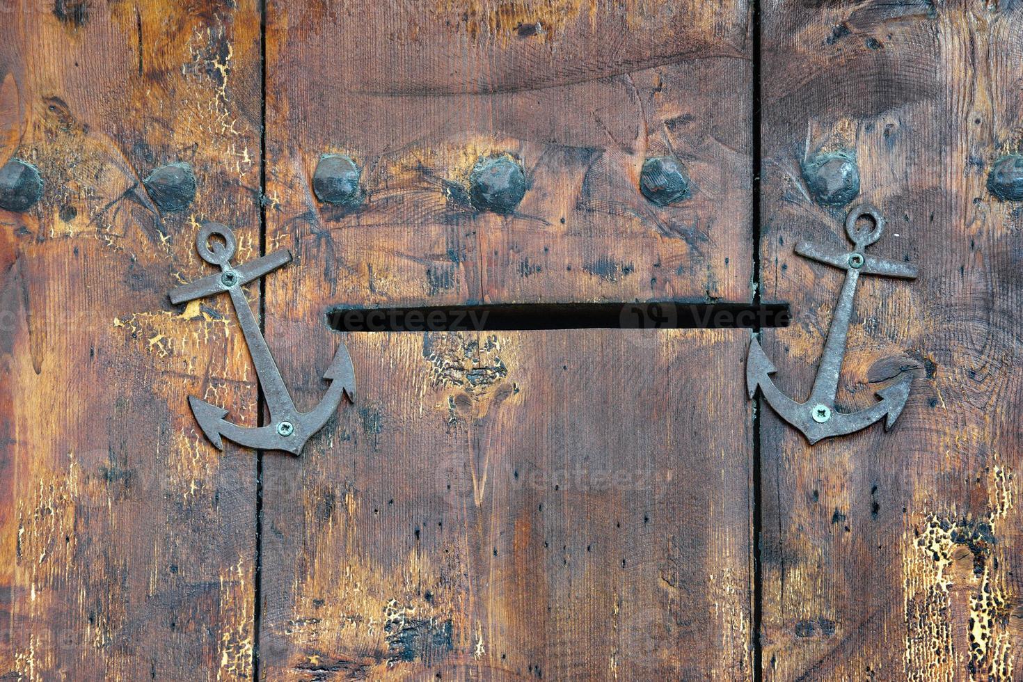 vecchia porta di legno con slot per posta e ancore foto