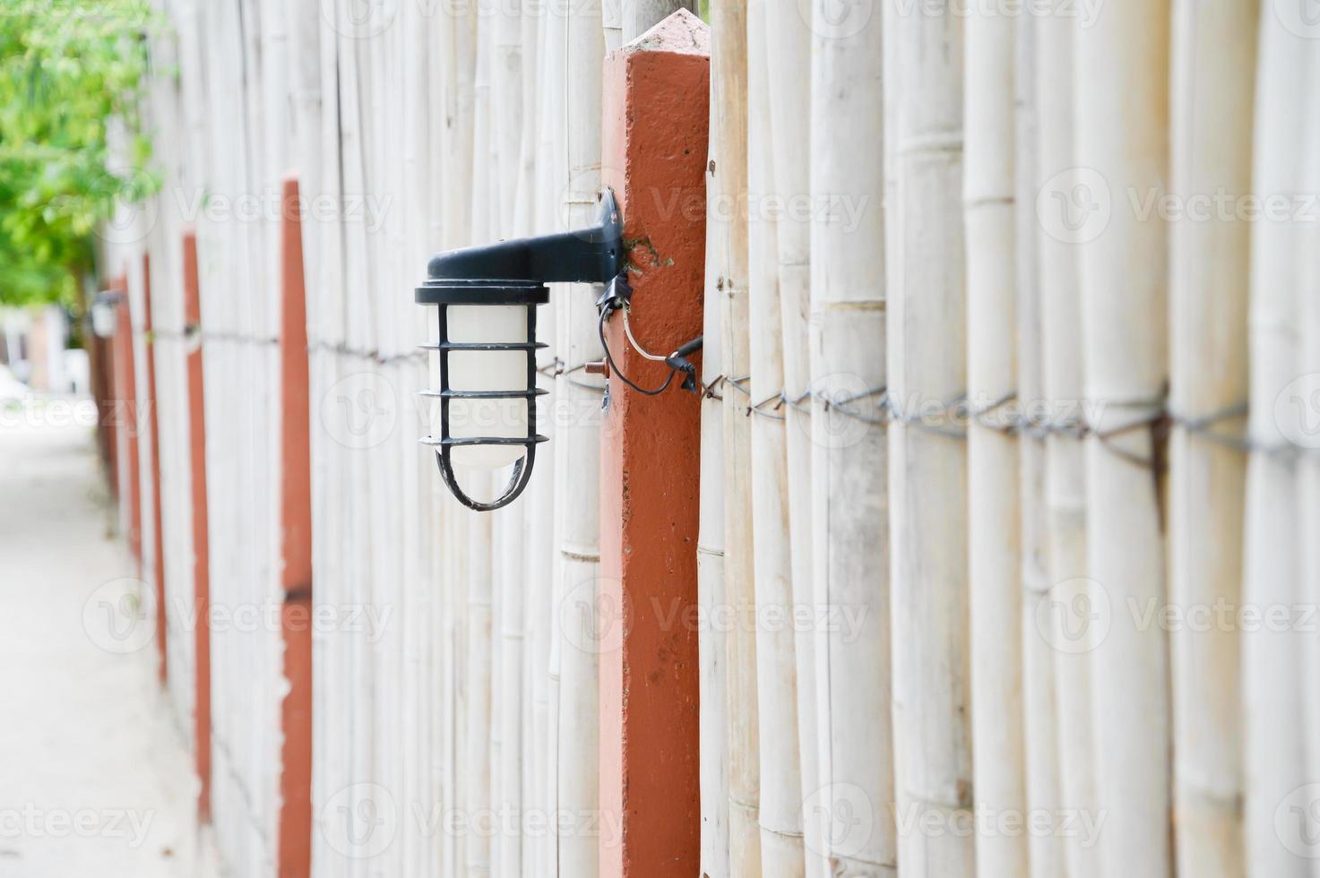 lampada da parete per esterni sulla recinzione di bambù nel parco foto