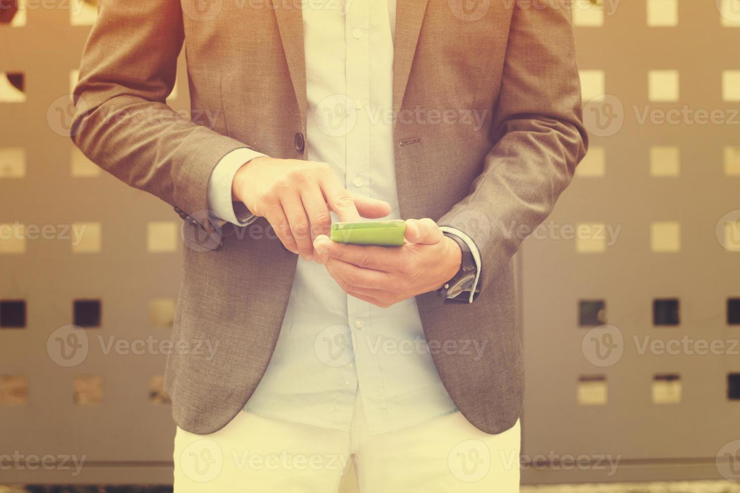 uomo elegante utilizzando il cellulare all'aperto. foto