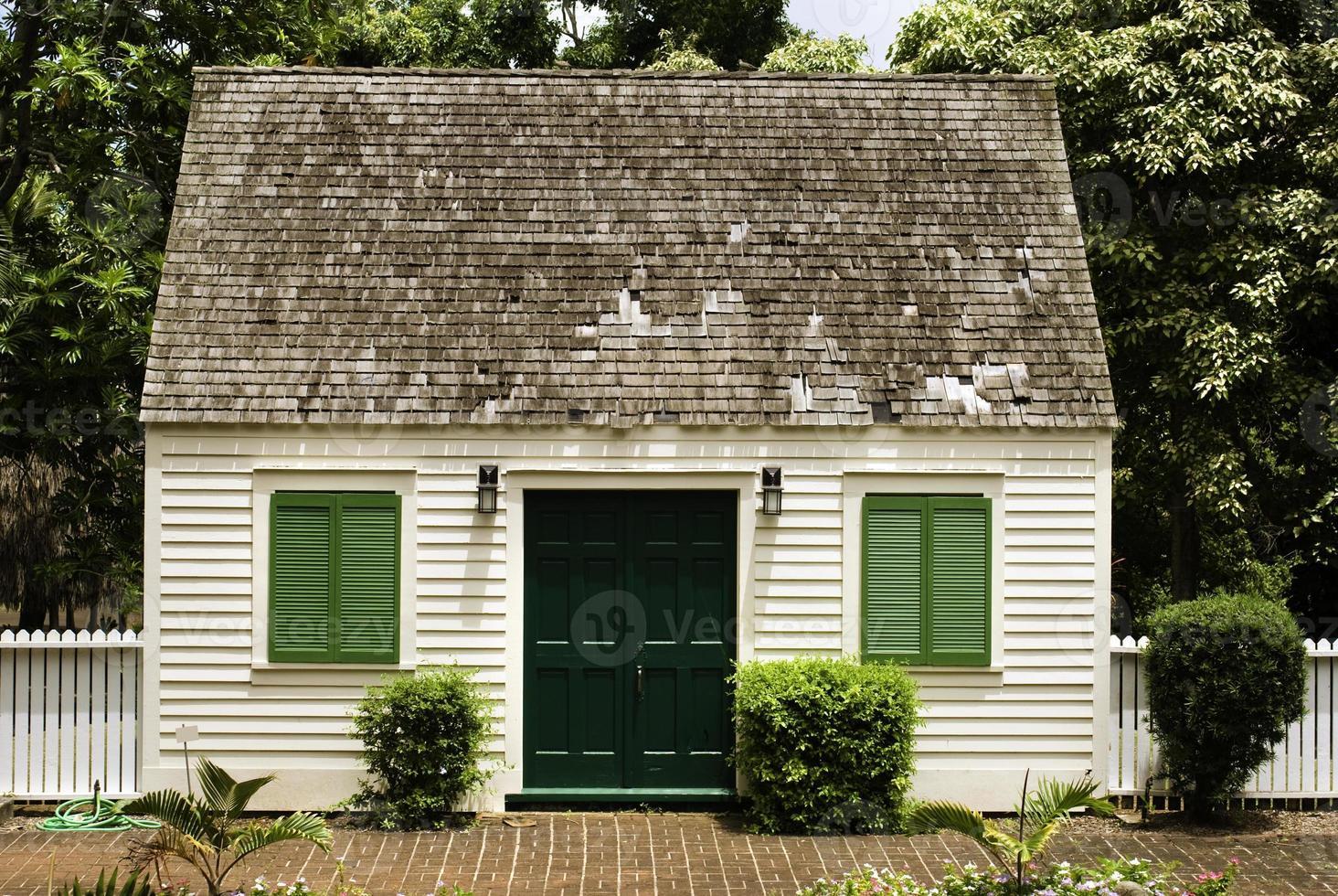 piccola casa con cortile in mattoni e staccionata bianca foto