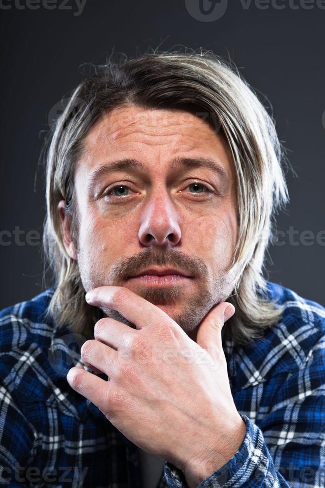 giovane espressivo con barba e capelli lunghi biondi. foto