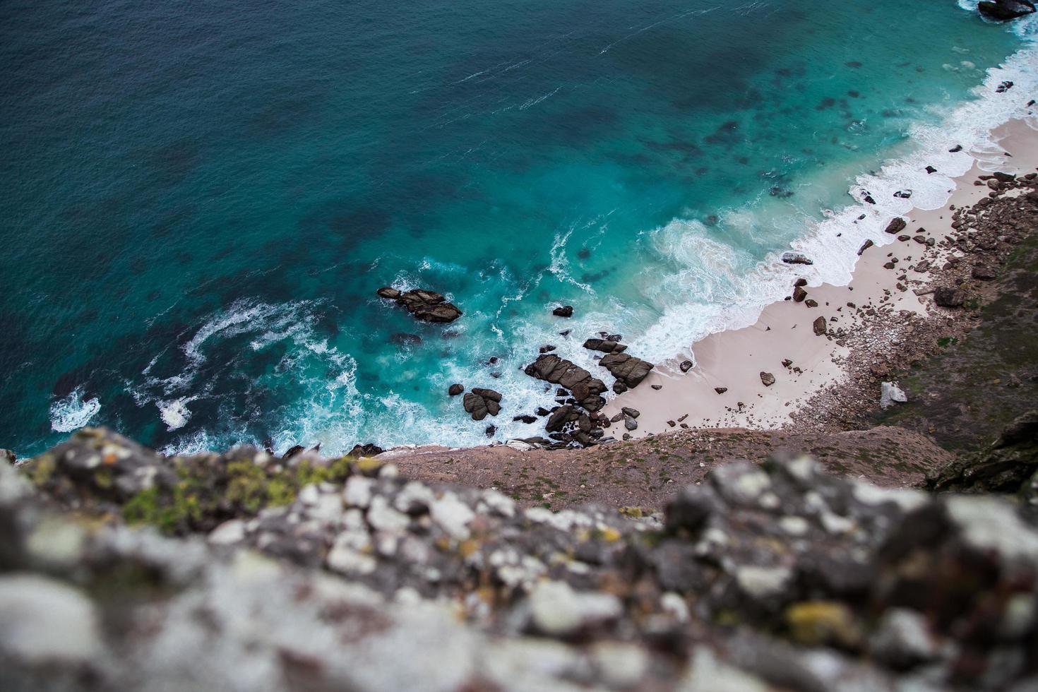 guardando in basso sulla spiaggia rocciosa foto