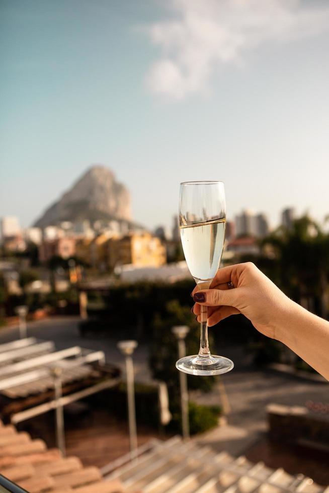 persona che tiene un bicchiere di vino bianco foto