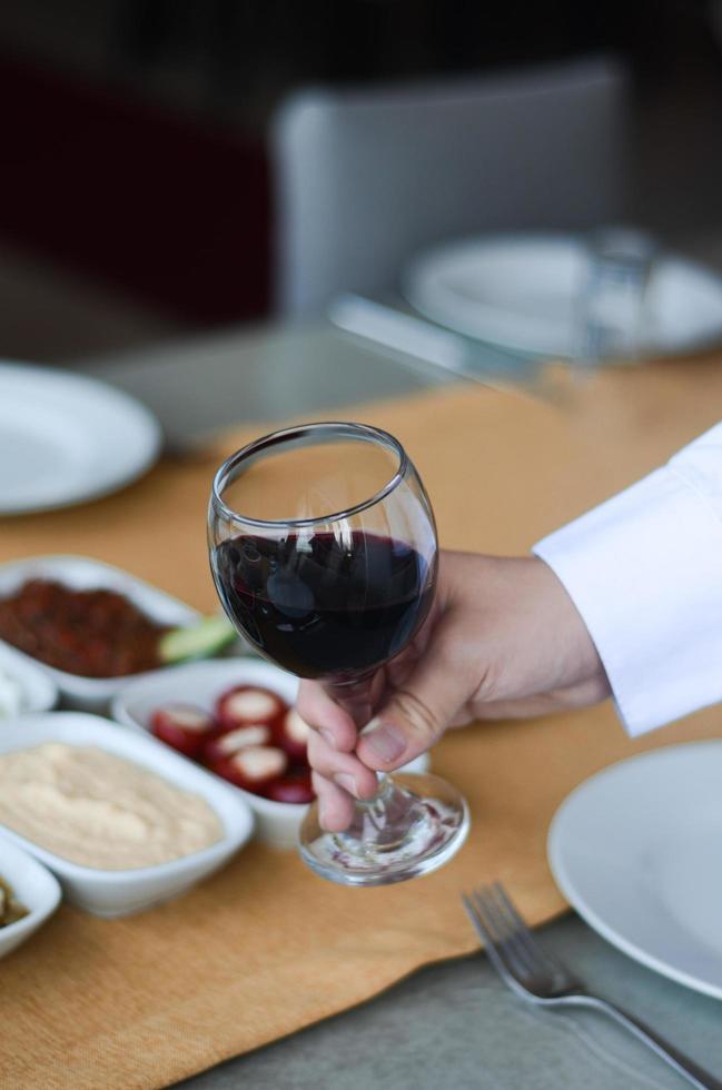 persona che tiene un bicchiere di vino foto