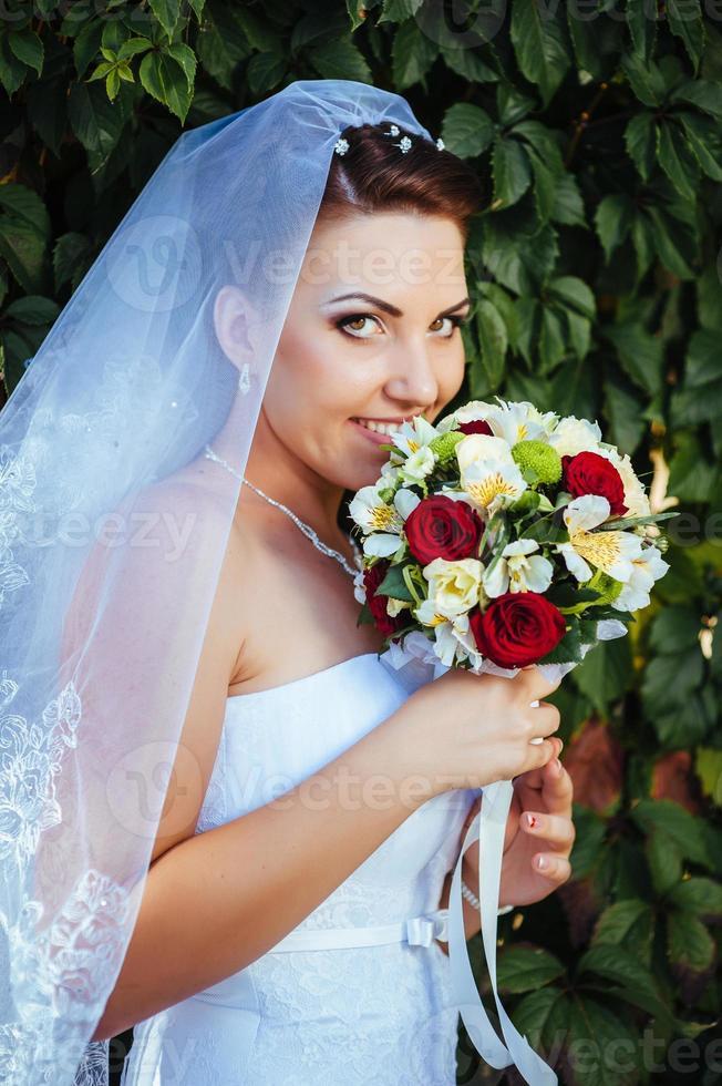 bella giovane sposa che tiene luminoso mazzo di fiori nelle mani foto