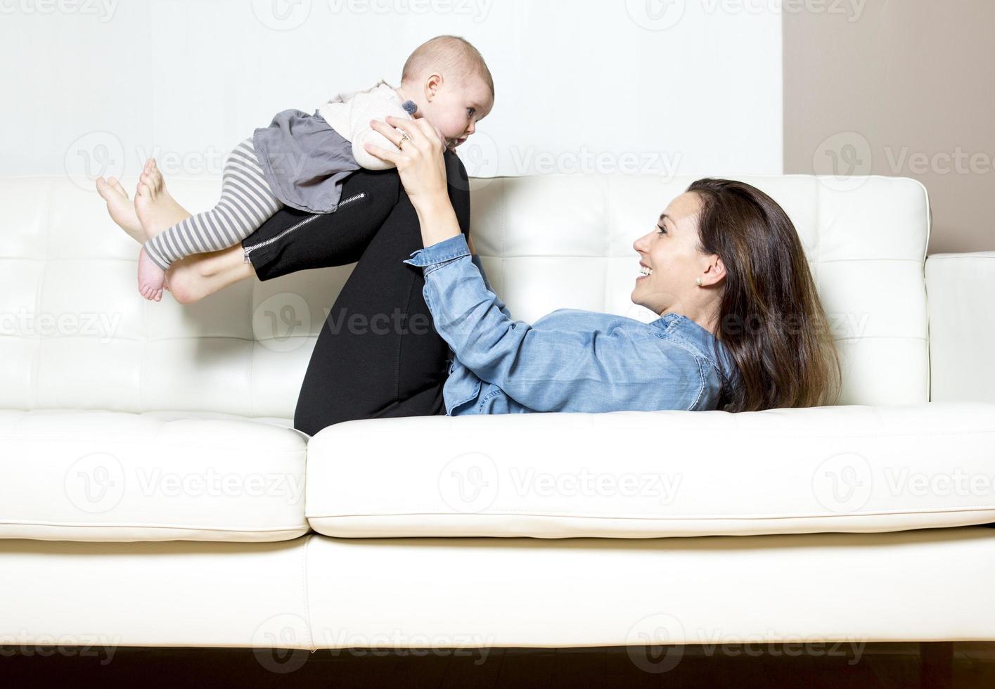 madre con bambino sul divano prendendo tempo foto