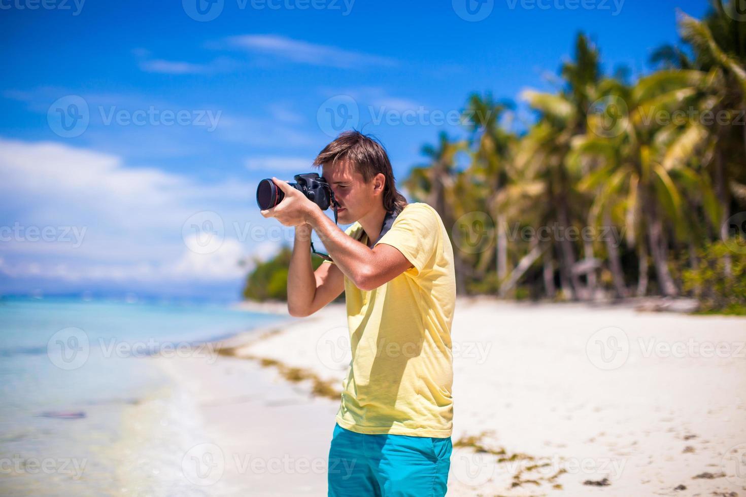 giovane che cattura le immagini sulla spiaggia tropicale foto