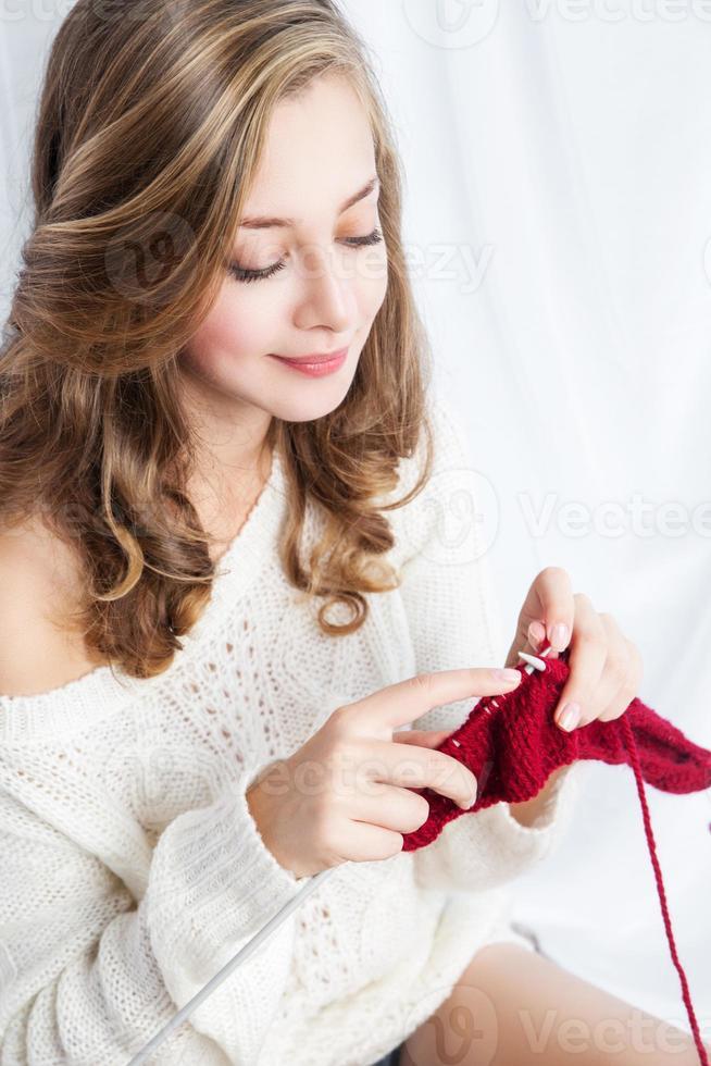 ragazza in maglione seduto sul davanzale della finestra e lavoro a maglia foto