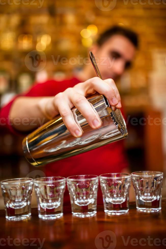 primo piano del barman versando bevande alcoliche e cocktail foto