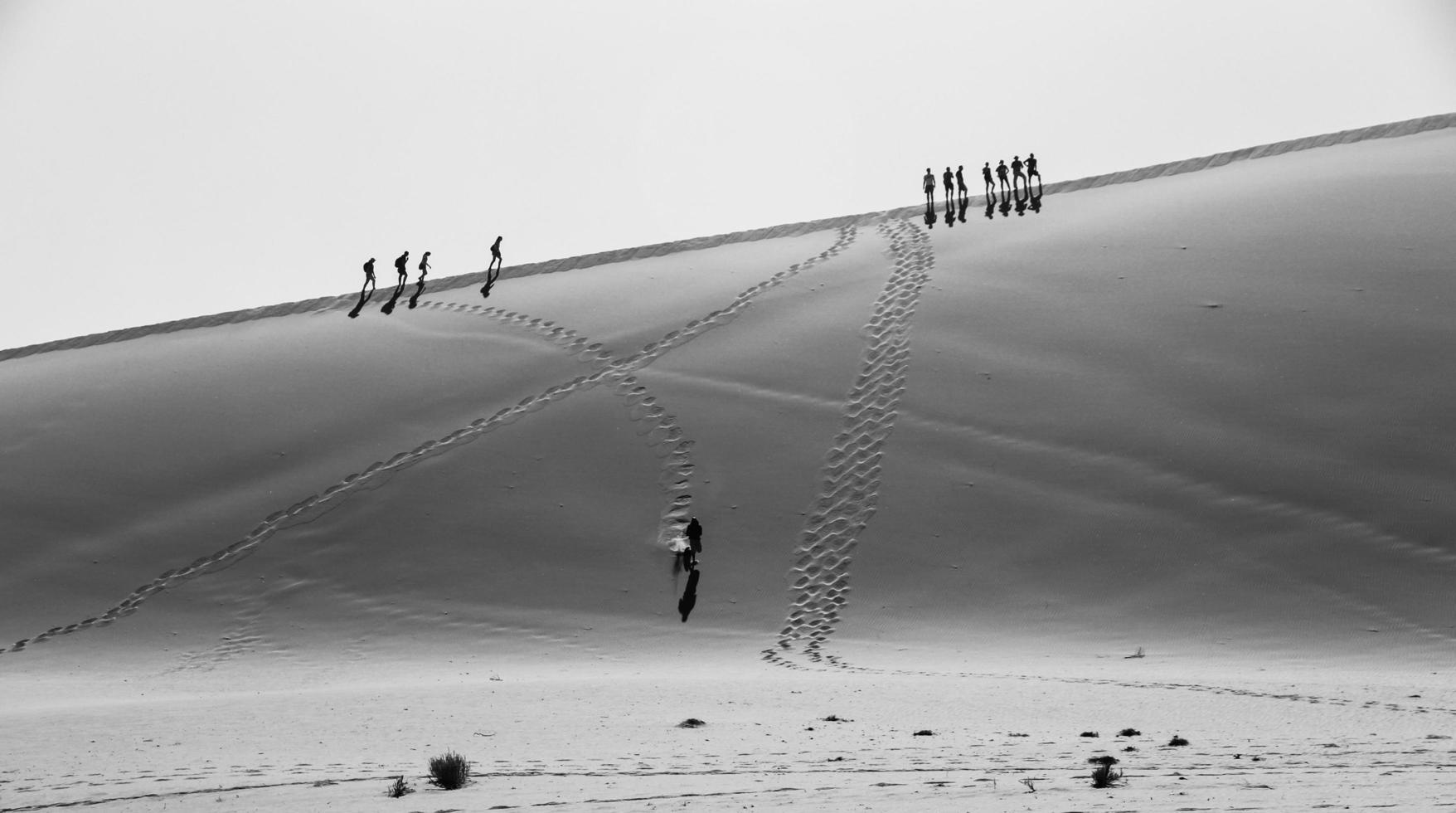 foto in scala di grigi di persone che camminano sul deserto
