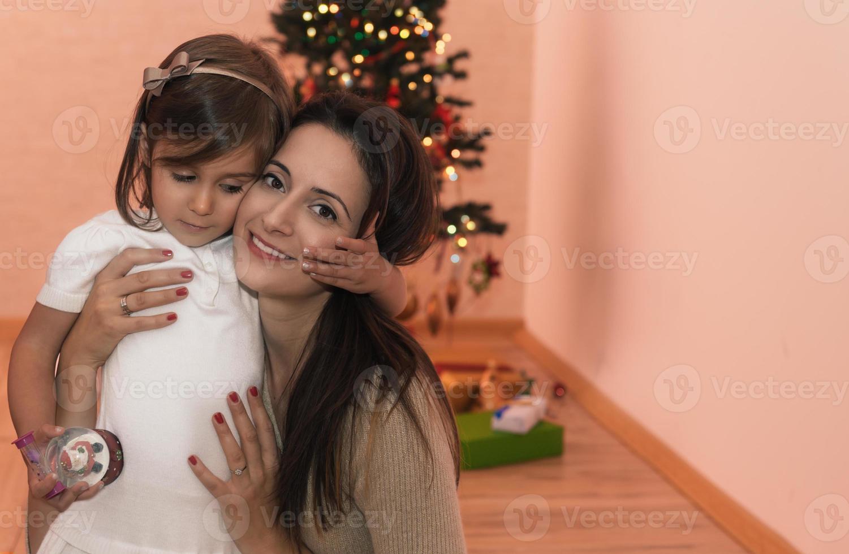 madre e figlia seduti davanti all'albero di Natale foto