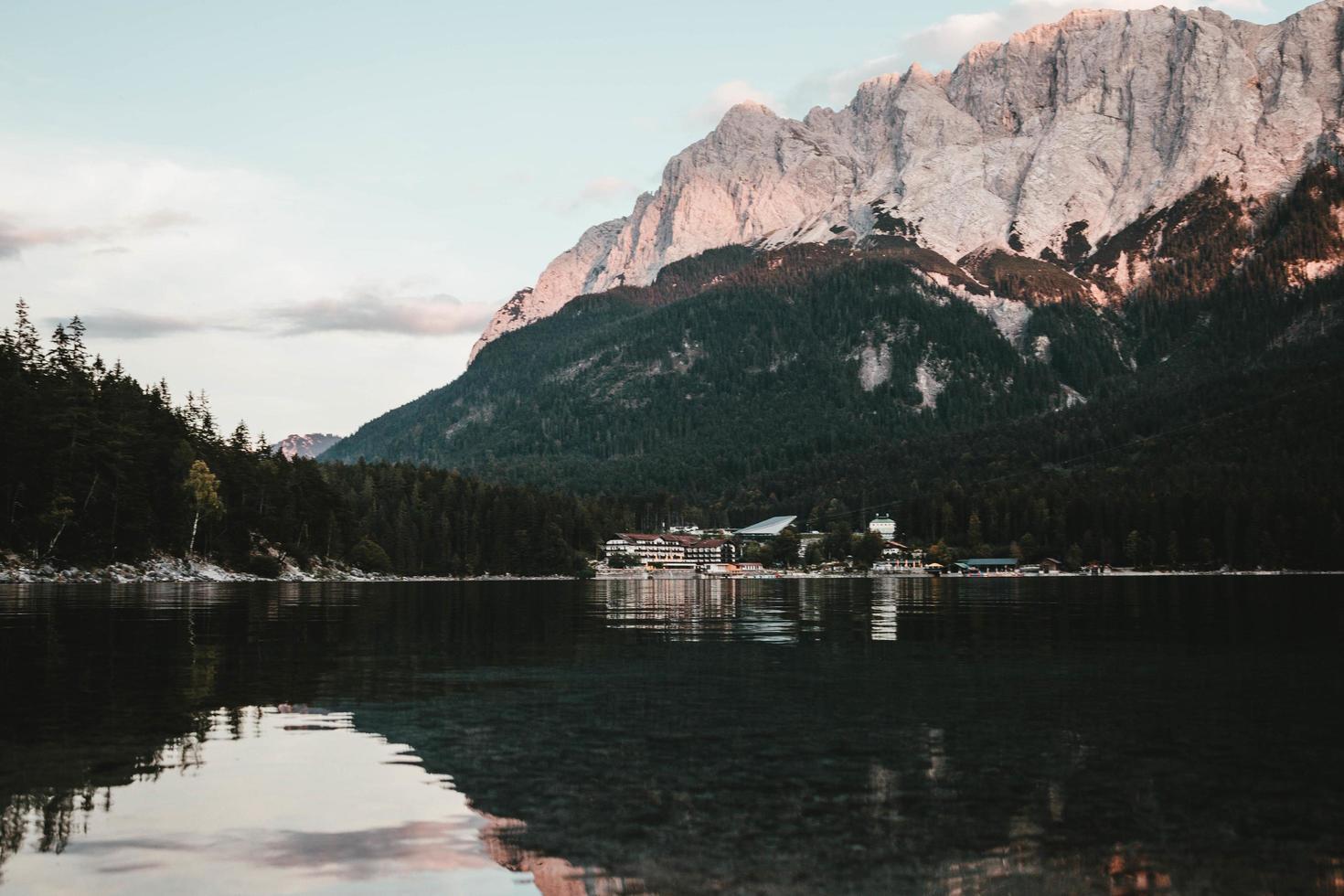 lago calmo e limpido con vista su alberi e montagne foto