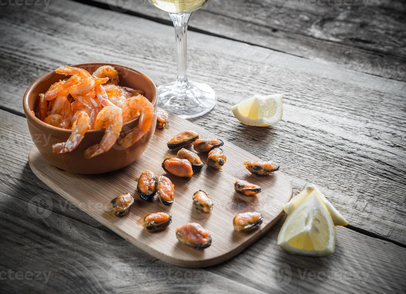 gamberi e cozze fritti con un bicchiere di vino bianco foto