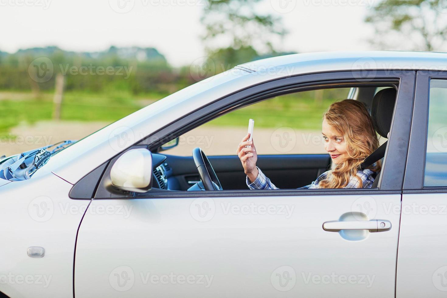 giovane donna alla guida di un'auto e utilizzando il telefono foto