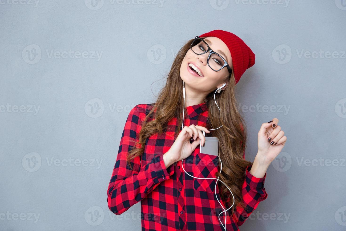 donna sorridente ascoltando musica in cuffia foto