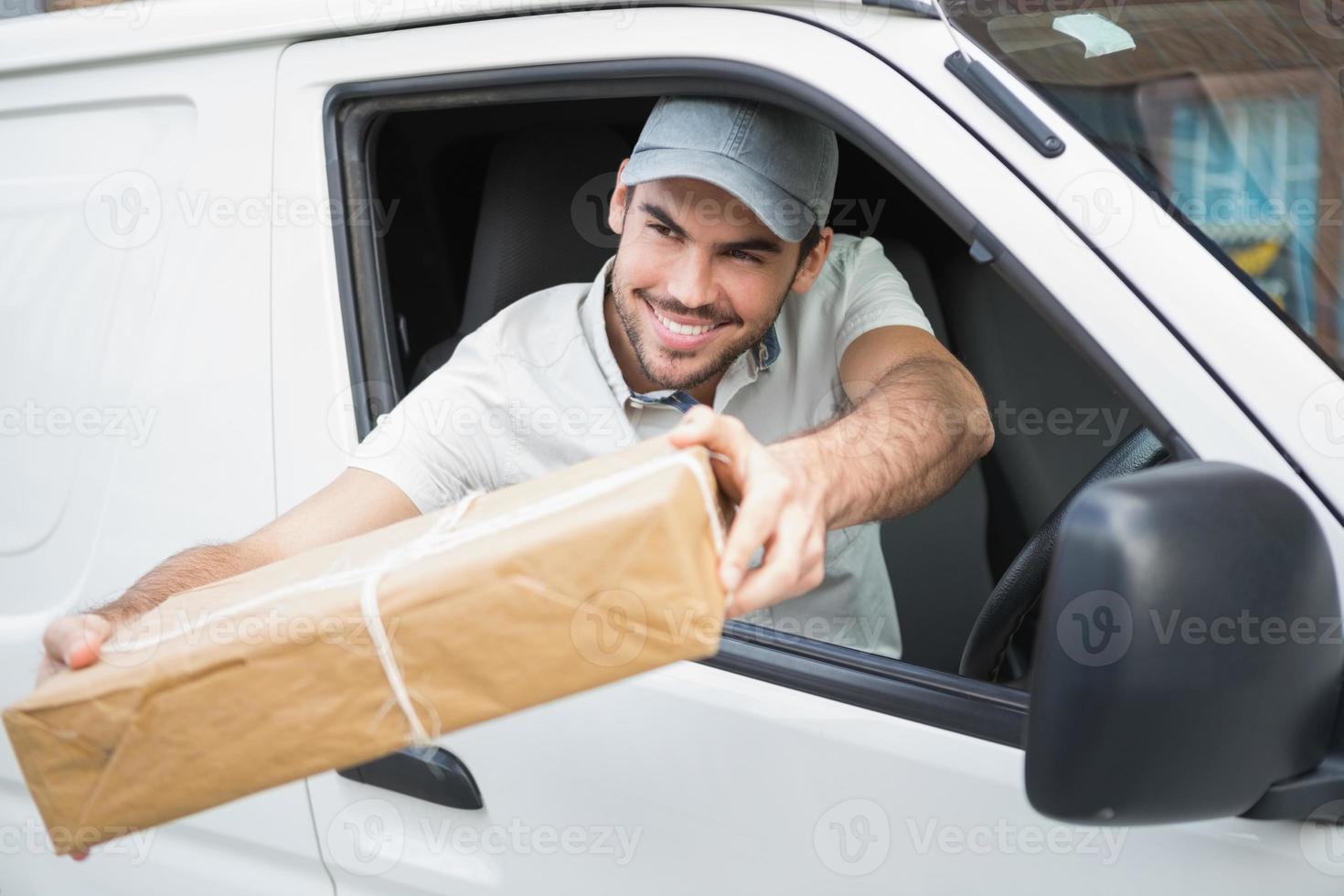 autista di consegna che offre il pacco dal suo furgone foto