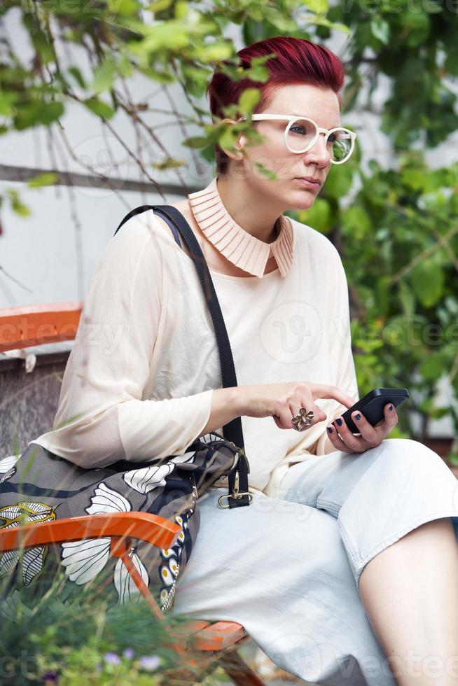 donna dai capelli rossi che manda un sms sul telefono foto