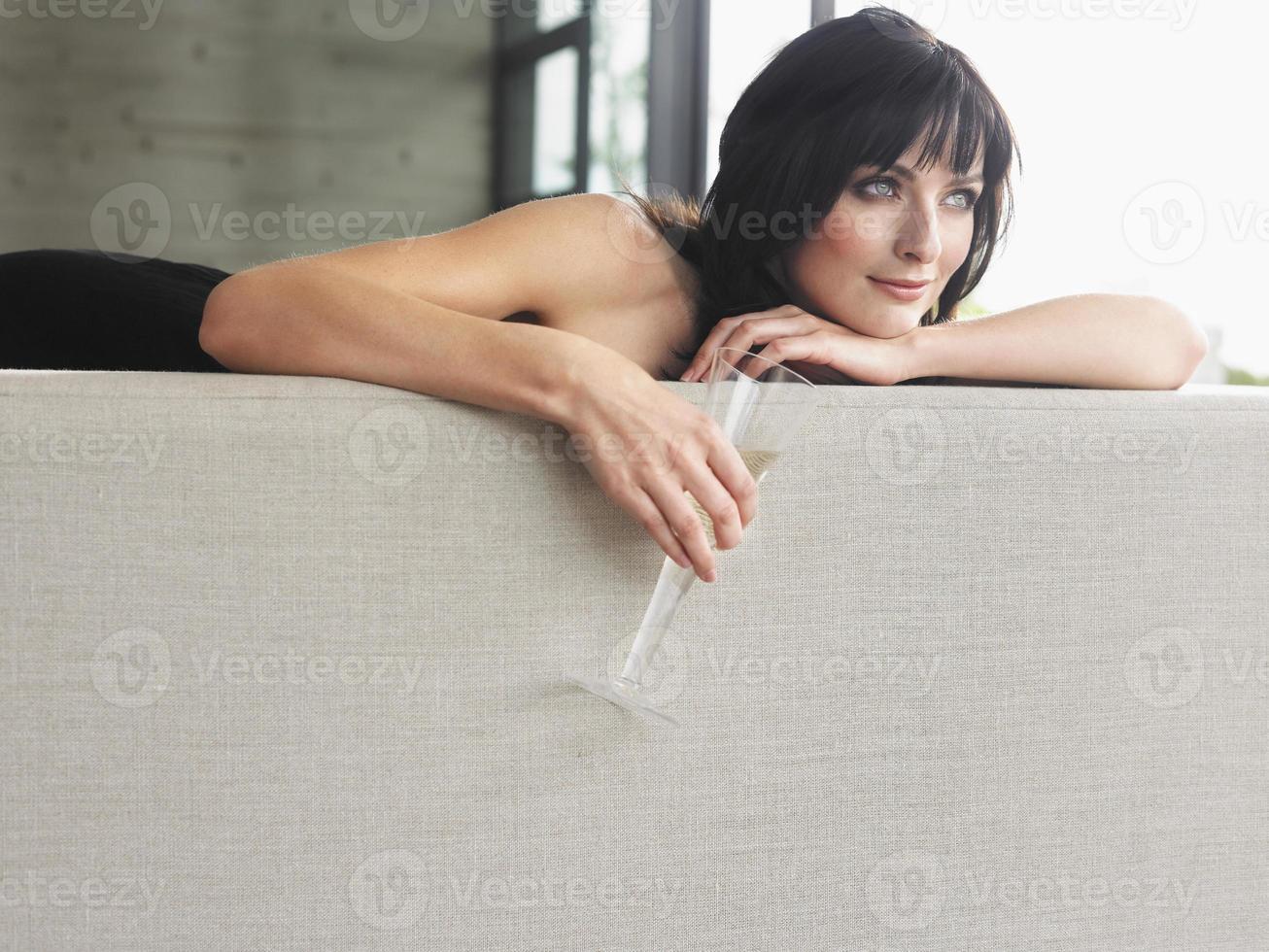 donna con un bicchiere di champagne sul divano foto