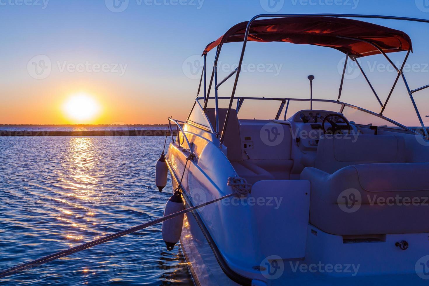 yacht vicino al molo contro il tramonto foto