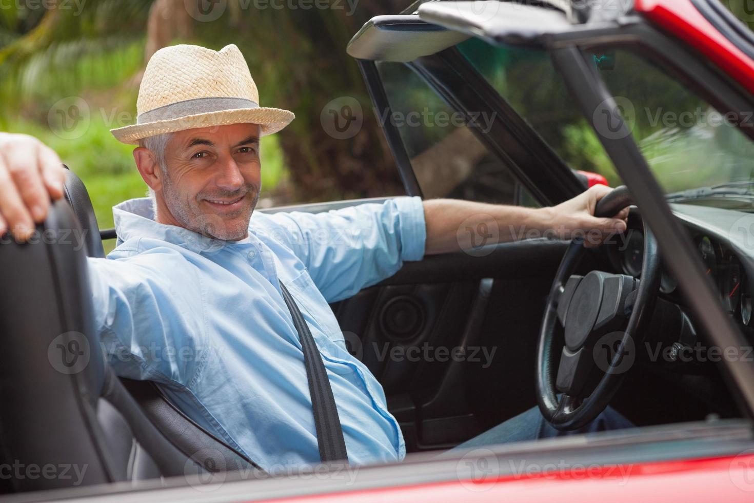 uomo bello sorridente che posa in decappottabile rossa foto