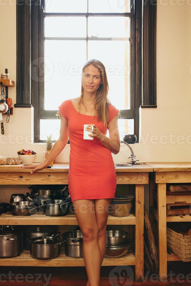 attraente giovane donna in cucina con una tazza di caffè foto