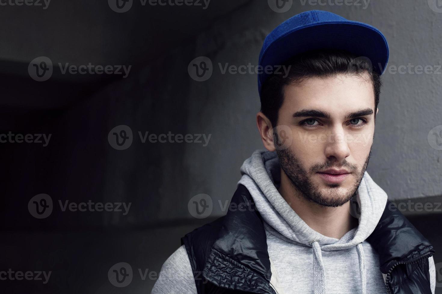 un ritratto di un giovane in una stanza grigia foto